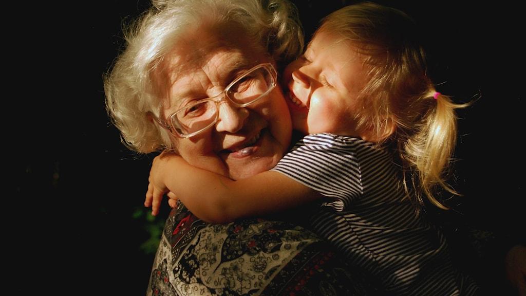 En liten tjej kramar en äldre dam.