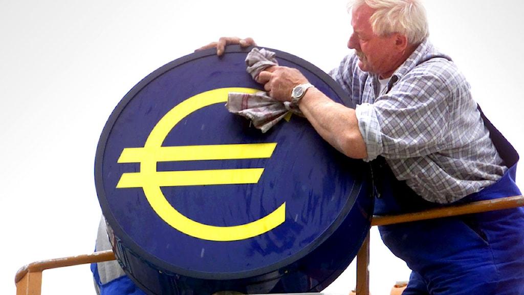 En man putsar ett euromärke. Foto: Frank Rumpenhorst/Scanpix.