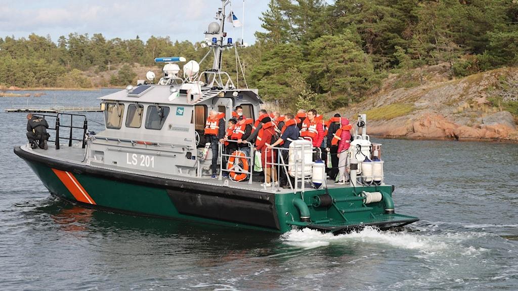 Passagerare evakueras från fartyget med hjälp av mindre båtar.