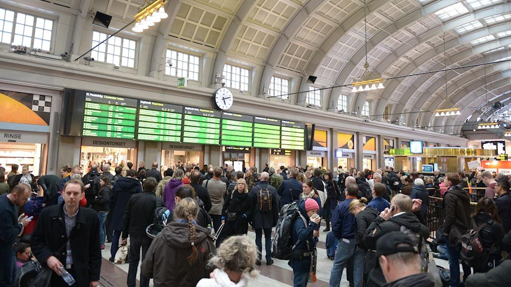 Tågresenärer studerar informationstavlan på Stockholm central med de försenade avångstiderna.