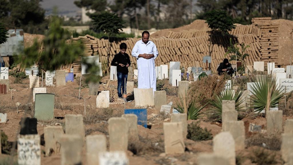 En syrisk man och son står vid grav i Douma