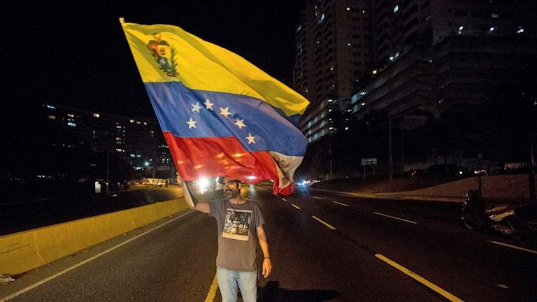 Man som viftar med en venezolansk flagga