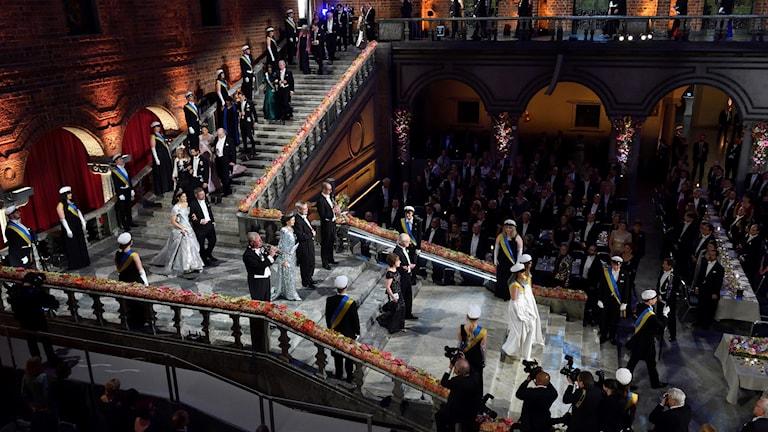 Festklädda människor går nerför en trappa.