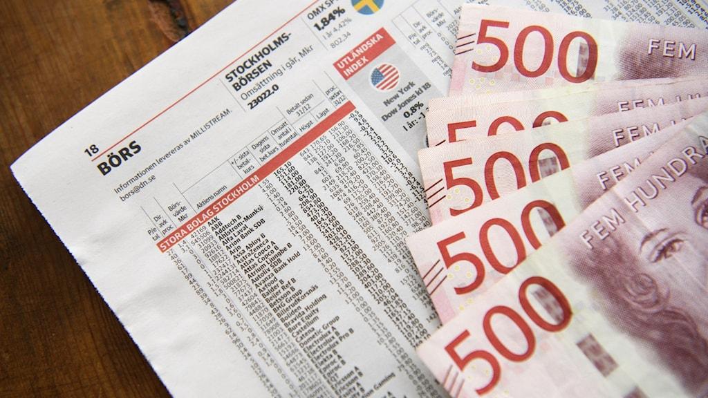 500-lappar som ligger på börssidorna i en tidning.