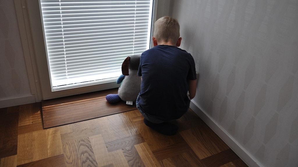 Barn som sitter i ett hörn med sitt mjukisdjur.