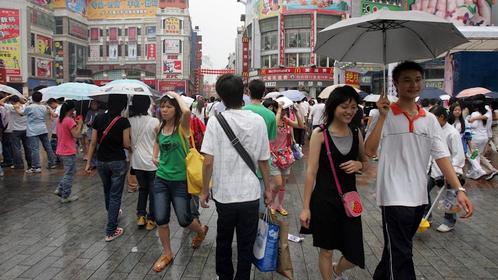 Människor i regnet på en bazargata i den kinesiska staden Guangzhou.