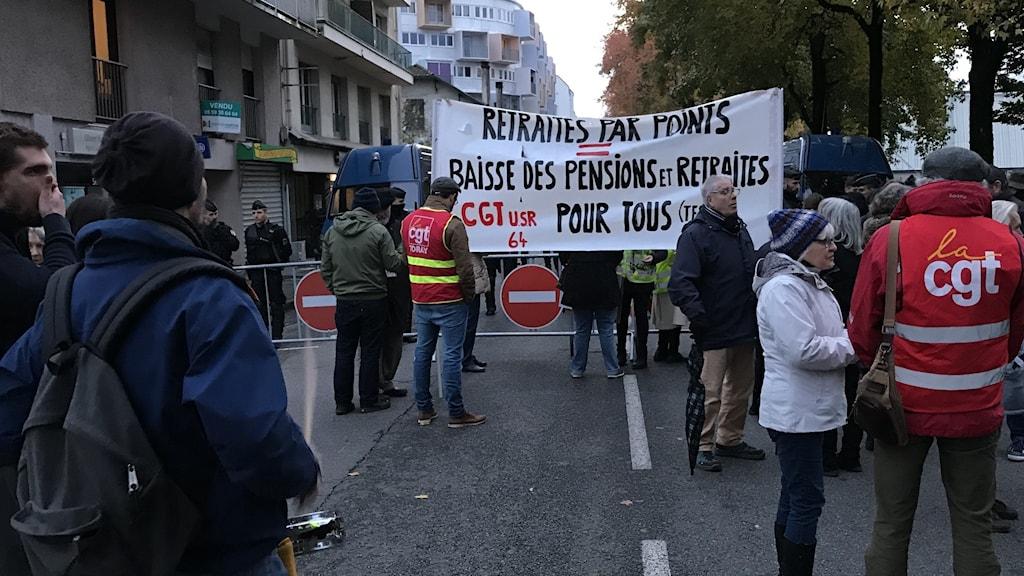 Demonstranter protesterar emot den franska  pensionsreformen utanför mässhallarna i Pau där frågan diskuterades en kväll i november.