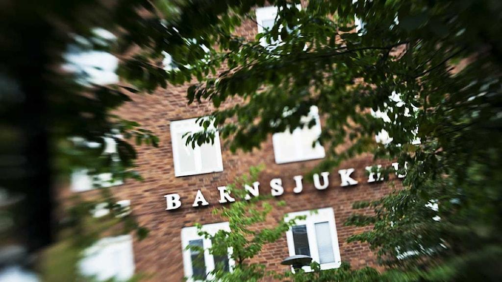Mellan trädgrenar ser man skylten till Astrid Lindgrens barnsjukhus 16*9