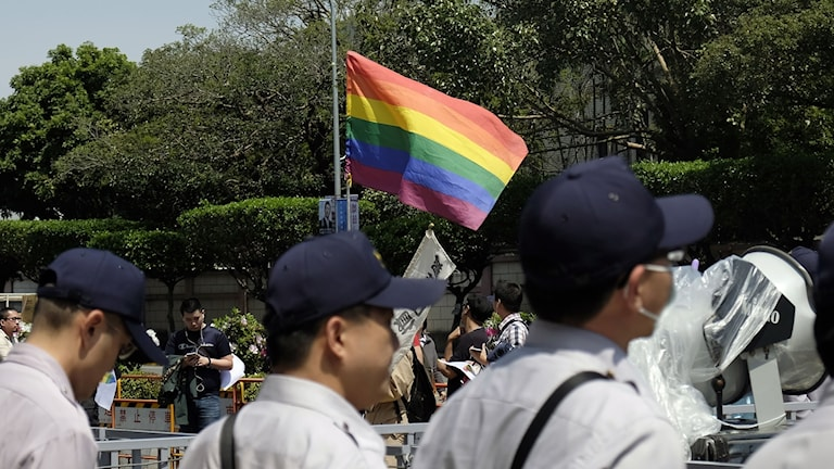 Prideflagga med tre män.