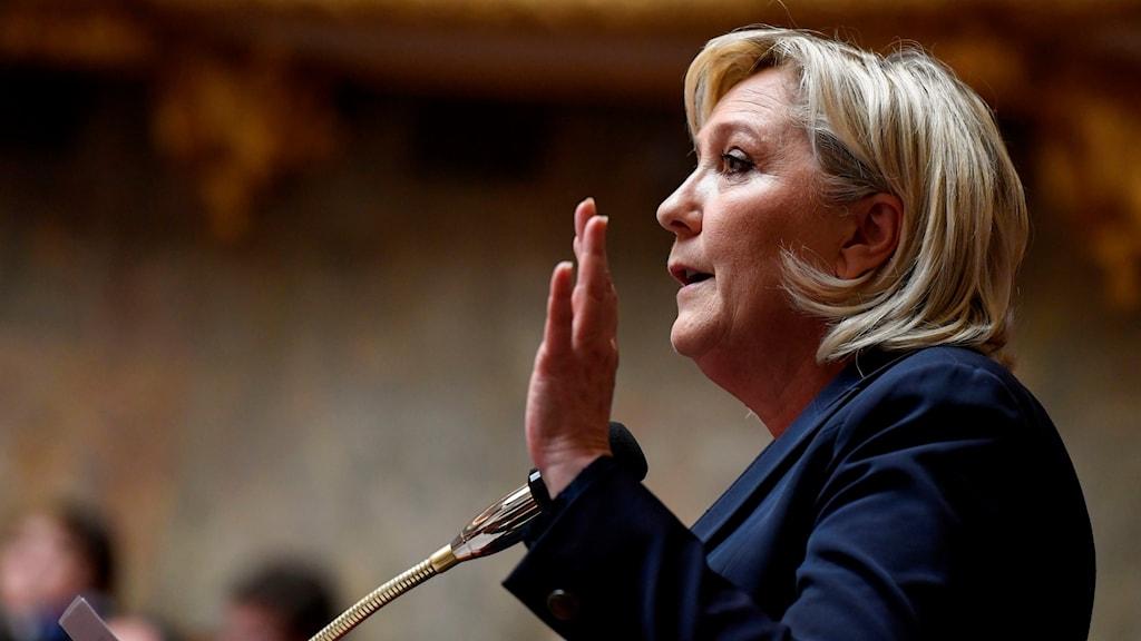 Blond kvinna i profil håller upp vänster hand.