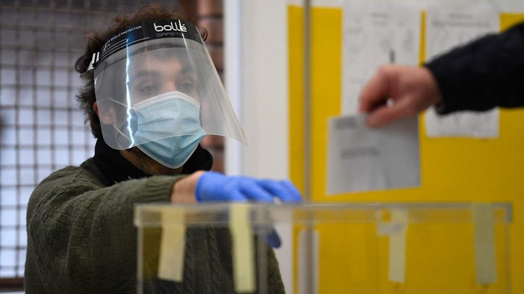 En person med visir vid en genomskinlig box där man stoppar valsedlar
