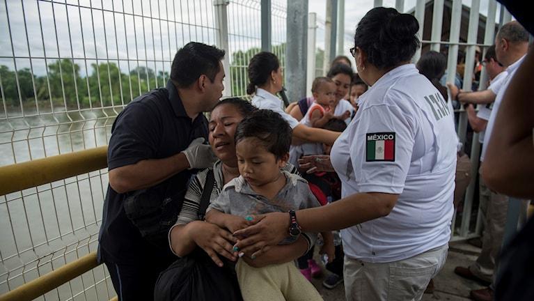 En honduransk kvinna och hennes son går över gränsen mellan Guatemala och Mexiko.