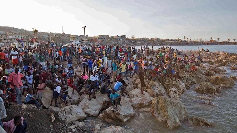 Invånare i i Jeremie väntar på stranden när en båt med vatten och mat från välgörenhetsorganiationen Hoppets Stjärna anländer på lördagen lördag.