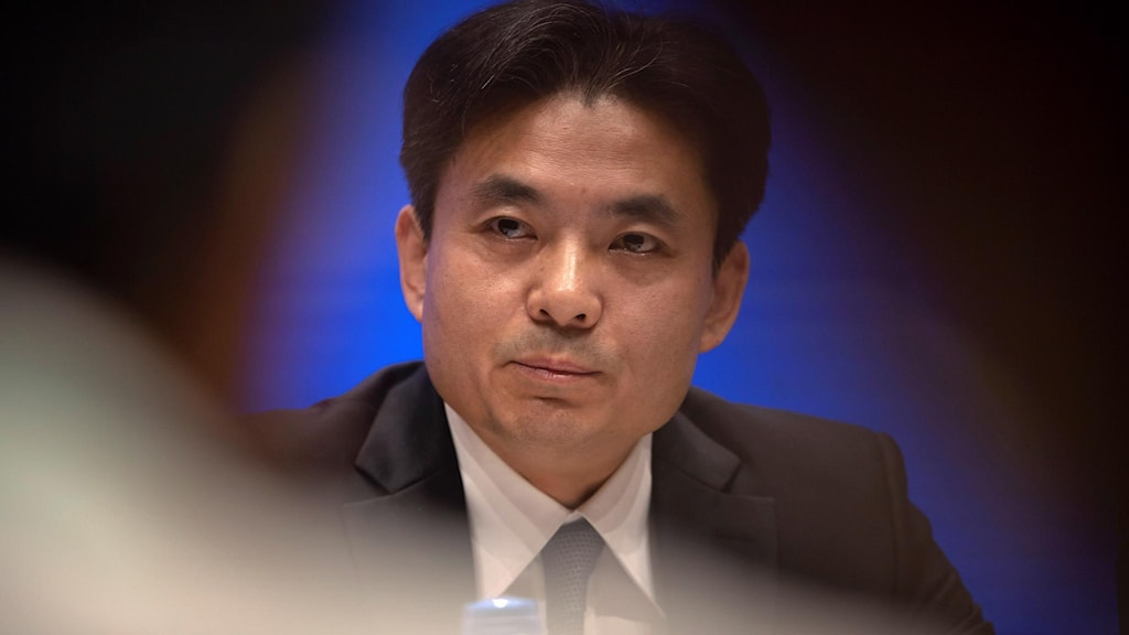 Yang Guang sitter på ett podie under presskonferensen
