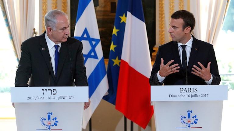 Benjamin Netanyahu och Emmanuel Macron står framför en israelisk och en fransk flagga.