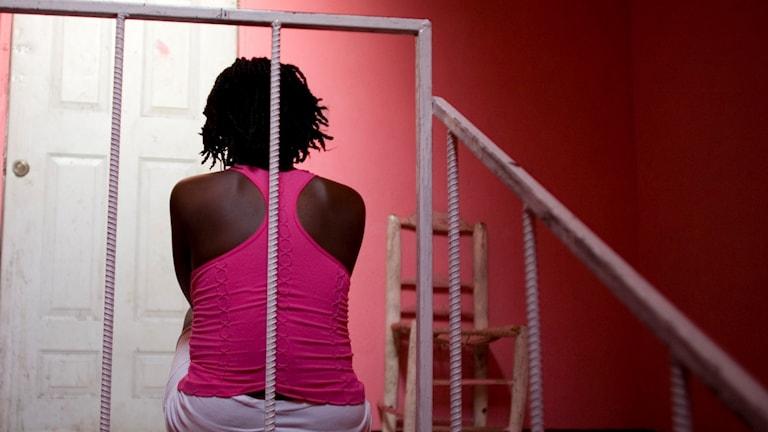 Person sitter med ryggen mot bild i en trappa