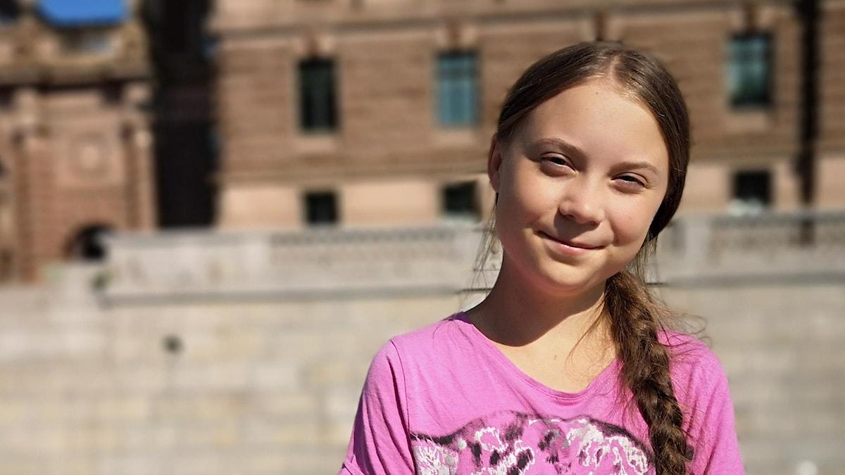Greta Thunberg framför riksdagen i Stockholm.