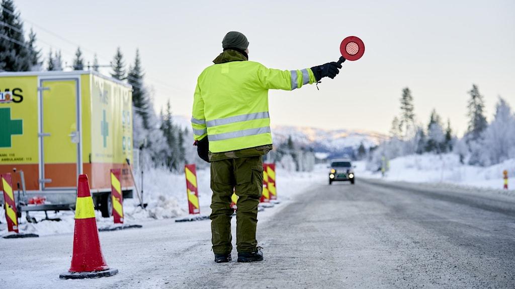 En gränsvakt står på vägen iklädd en gul reflexjacka och stoppar en bil.