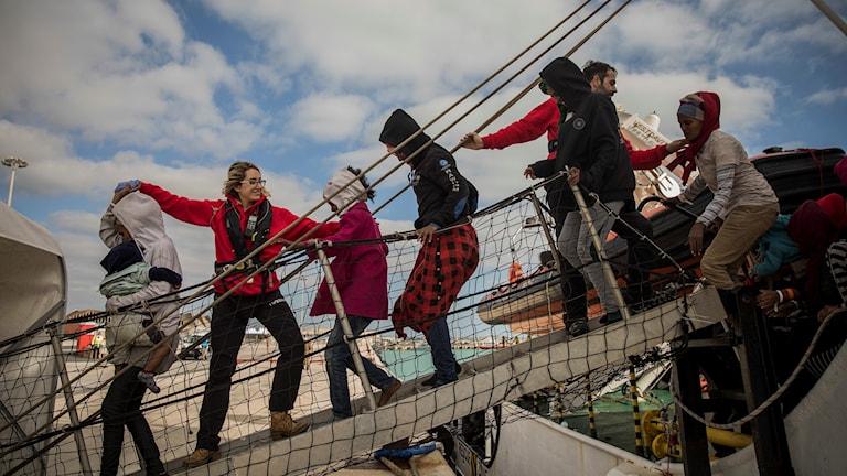 En grupp migranter får hjälp att ta sig i land i en hamn på Sicilien i Italien.
