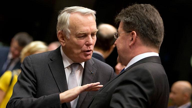 Två män står och pratar, ser hetsigt ut