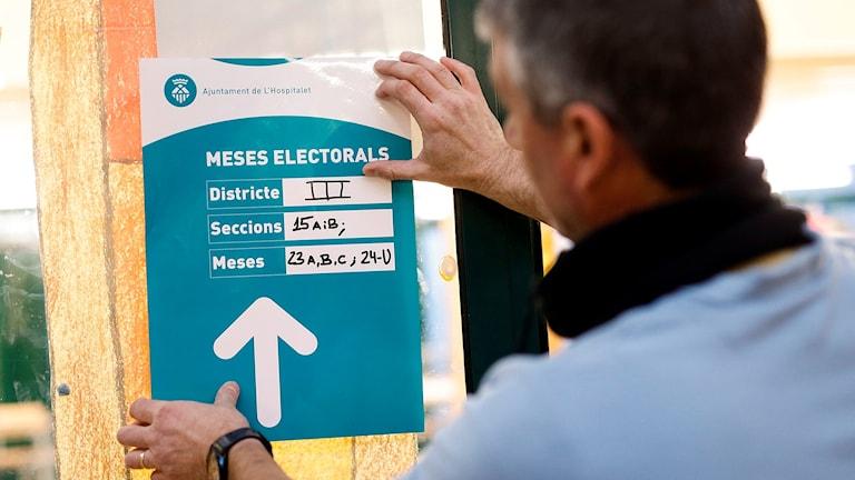 En man sätter upp en lapp utanför en av vallokalerna.