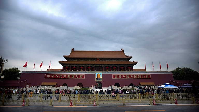 Visitors stand outside the Tiananmen Gate next to Tiananmen Square in Beijing