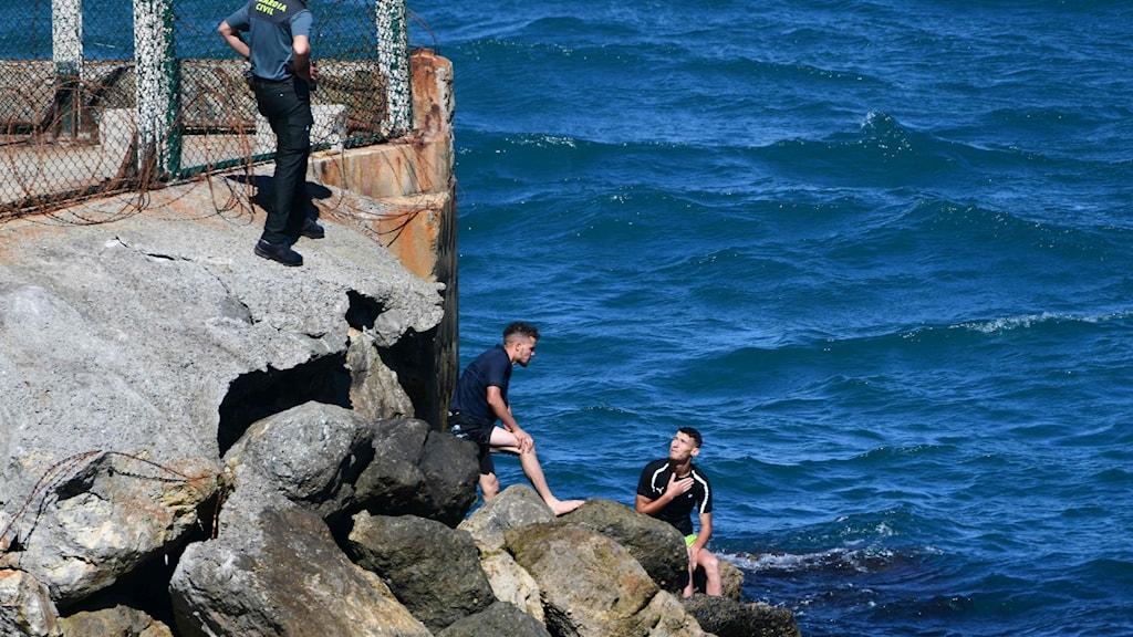 Två män i vattenbrynet pratar med en vaktklädd person uppe på strandkanten.