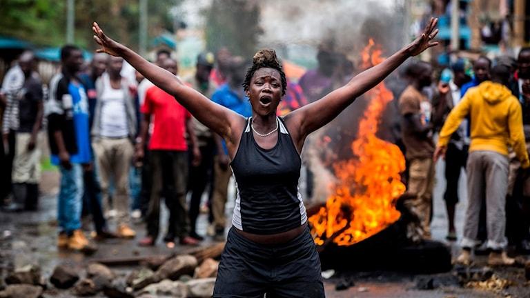 En kvinna står framför en eld