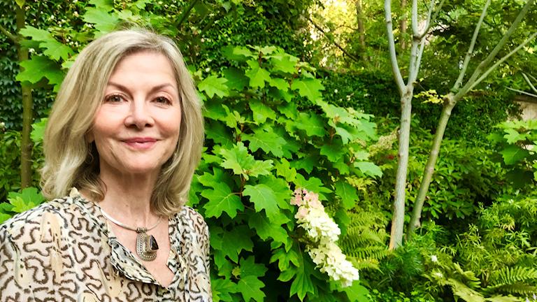 Kvinna framför gröna träd.