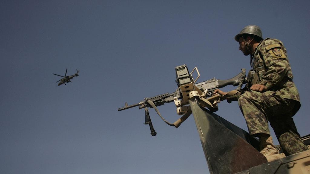 Man med kulspruta mot en blå himmel. Helikopter ovanför i luften.