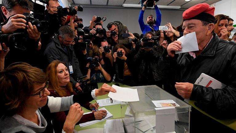 En man som bär en traditionell katalansk huvudbonad kysser sin röstsedel i Barcelona.
