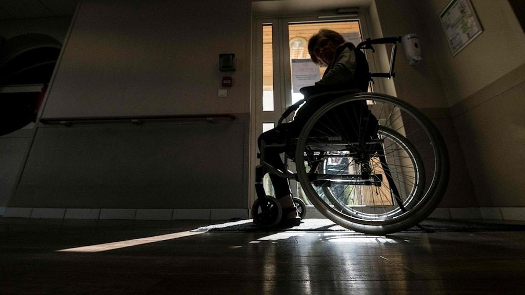 äldre person i rullstol i mörkt rum