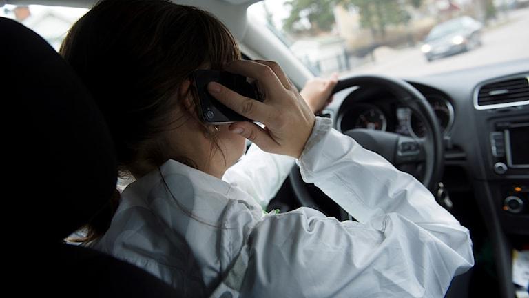 Kvinna kör bil och pratar i mobilen samtidigt.