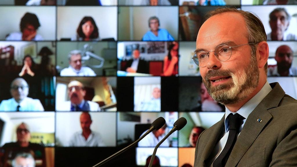 Skallig man med skägg och glasögon talar framför storskärm med en mängd mötesdeltagare