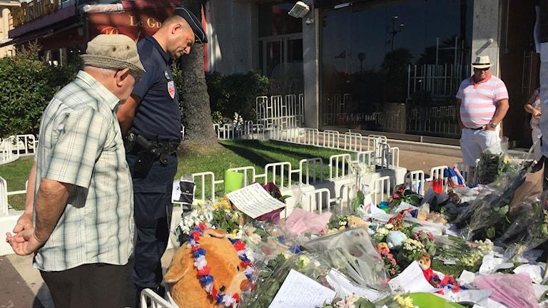 Sörjande människor i Nice som tittar på gåvor till offren