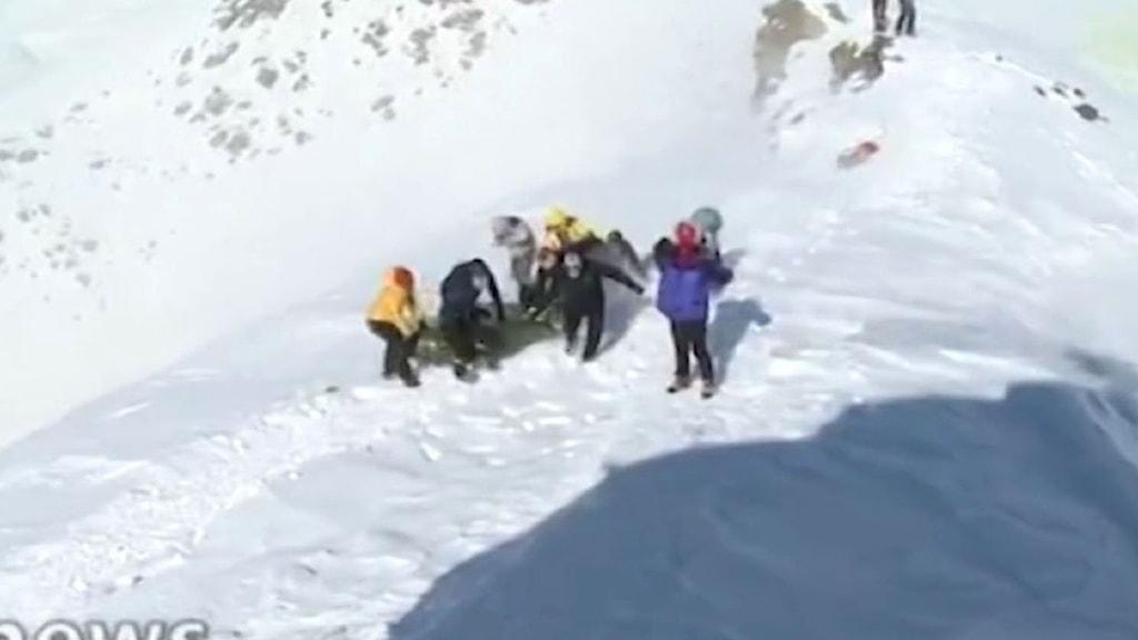 Räddningsarbetare står och gräver efter överlevande i snön