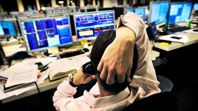 Börsmäklare vid flera datorskärmar