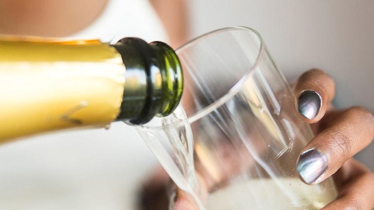 Kvinna häller upp champagne i glas