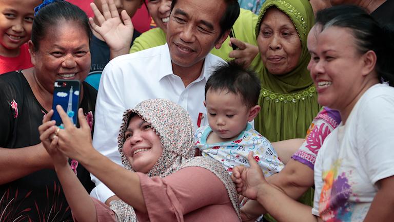 Indonesien val - kvinna tar en selfie med president  Joko Widodo. Foto: Dita Alangkara/TT.