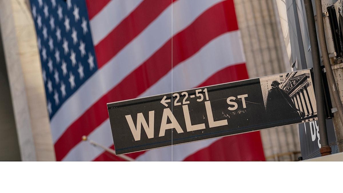 Gatuskylt med texten Wall st framför en amerikansk flagga
