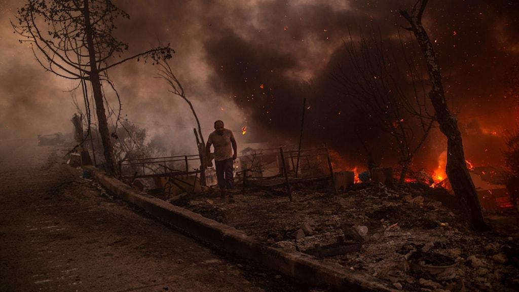 En man står i Moria-lägret på Lesbos. Meter ifrån honom rasar branden.