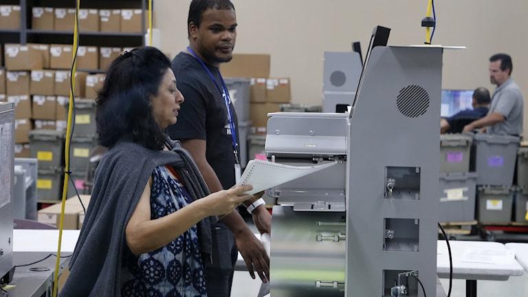 Kvinna matar in röstsedlar i en maskin