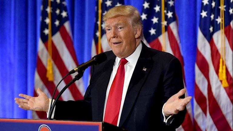 Trump ser förvånad ut och sträcker ut händerna vid talarstolen