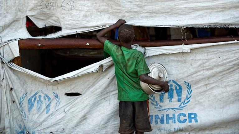 Pojke som tittar in i ett tält med texten UNHCR.