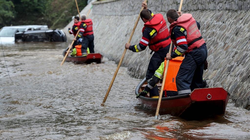 Räddningsarbetare letar efter människor i översvämningarna.