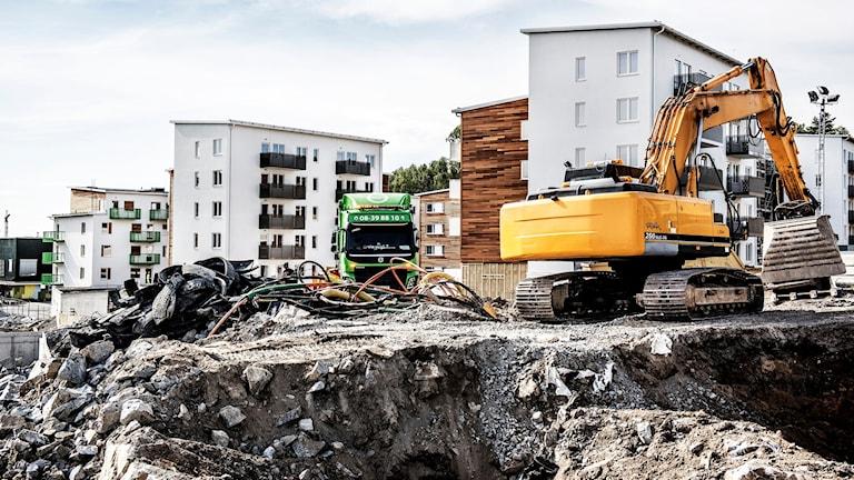 Grävmaskiner och bostadshus.