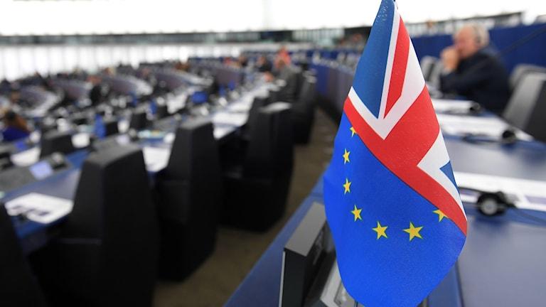 En halv EU-flagga och en halv brittisk flagga står på ett bord i Europaparlamentet i Strasbourg