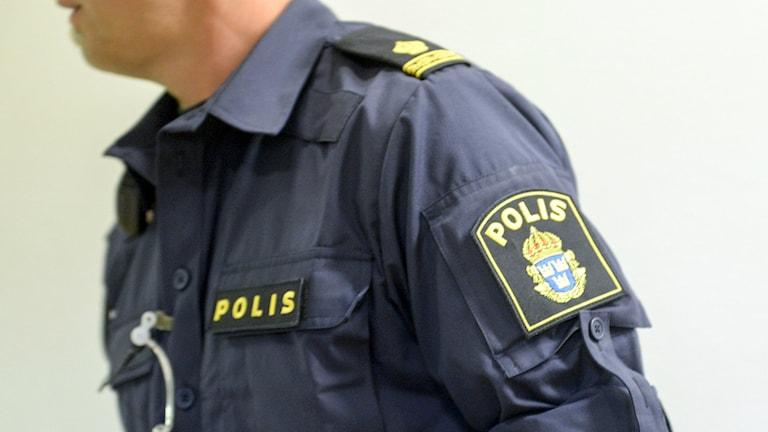 Bilden visar en polis i uniform. Man ser en del av armen och överkroppen. Foto: Bertil Ericson/TT.