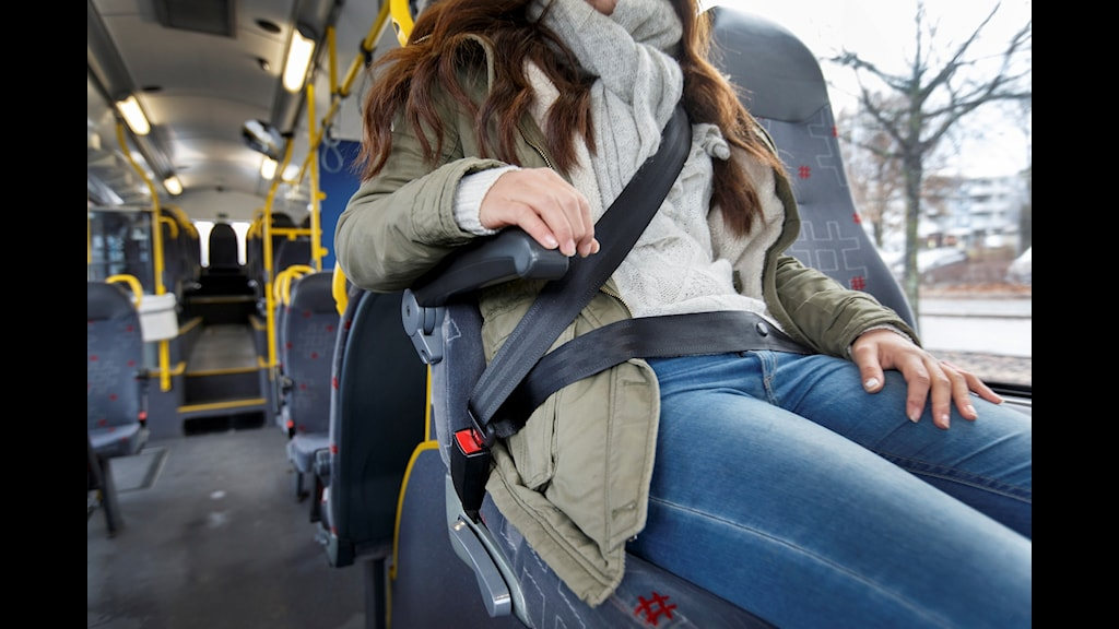 Kvinna sitter fast i säkerhetsbälte i en buss.