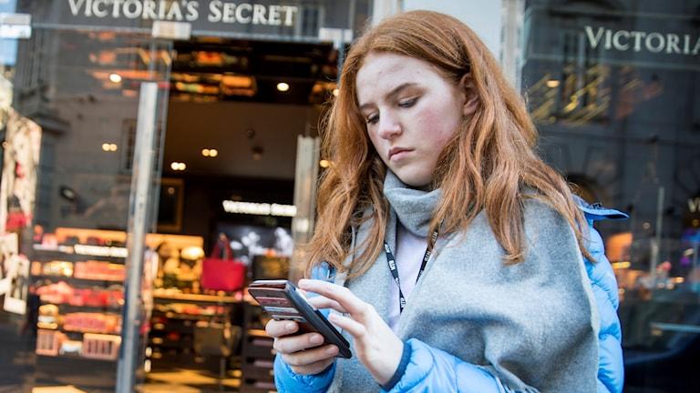Ung kvinna med mobil i handen.